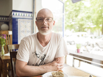 Germany, Berlin, Mature man sitting in cafe, looking at camera - TAM000224