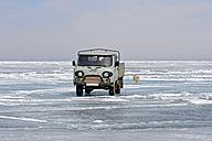 Russia, Lake Baikal, pickup truck and Siberian Husky on frozen lake - GNF001357