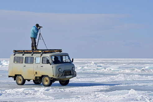 Russia, Lake Baikal, man with telescope standing on minibus on frozen lake looking out for seals - GN001360