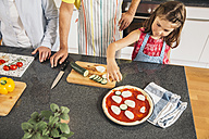 Little girl garnishing homemade pizza in the kitchen - MFF001754