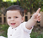 Portrait of smiling baby boy pointing his finger - RAEF000229