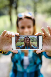 Smiling teenage girl taking a selfie with smartphone - GIOF000072