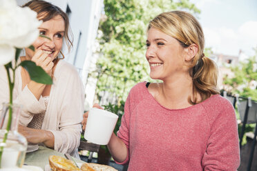 Two woman sitting at breakfast table on balcony - MFF001704