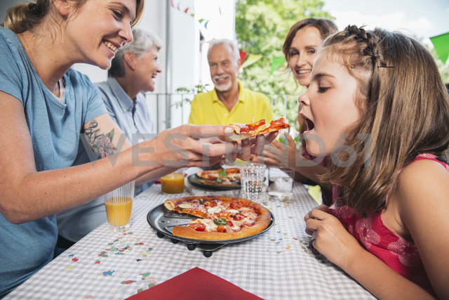 Girl being fed with homemade pizza at family party - MFF001711 - Mareen Fischinger/Westend61