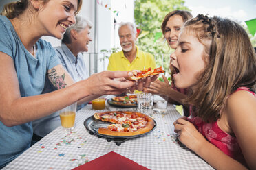 Girl being fed with homemade pizza at family party - MFF001711