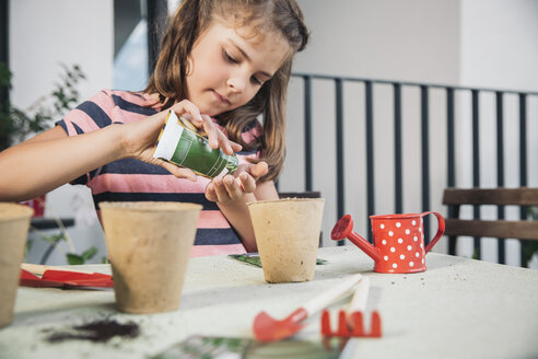 Little girl gardening with seeds and soil on balcony - MFF001782