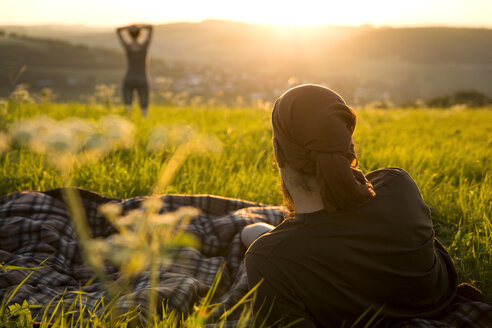 Germany, couple on a meadow watching for sunrise - MIDF000494