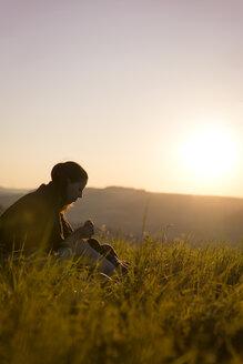 Germany, woman having breakfast on a meadow at sunrise - MIDF000497