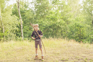 Germany, Saxony, Indians and cowboy party, Boy playing with bow and arrow - MJF001650