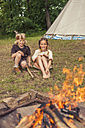 Germany, Saxony, Indians and cowboy party, Children sitting at bonfire - MJF001652