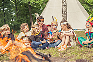 Germany, Saxony, Indians and cowboy party, Children sitting at bonfire - MJF001655