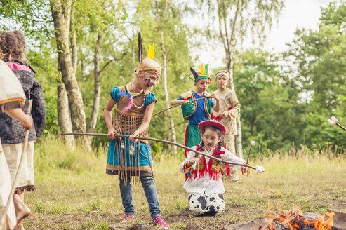 Germany, Saxony, Indians and cowboy party, Children rasting marshmallows on sticks - MJF001663