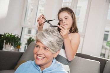 Girl cutting hair of her grandmother at home - MFF001687