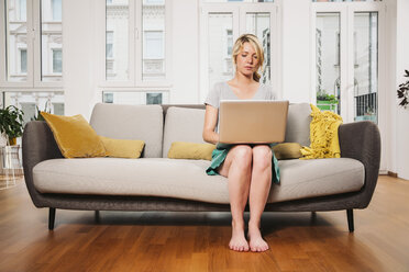 Woman sitting on a couch at living room using laptop - MFF001747
