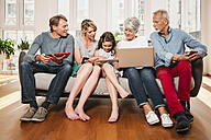 Group picture of three generations family with different digital devices sitting on one couch - MFF001750