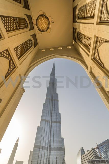 United Arab Emirates, Dubai, The Burj Khalifa framed by a historic arab arch in the evening light - NKF000266