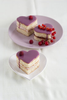Small biscuit cakes in heart shape with raspberry cream and currant jelly - MYF001072