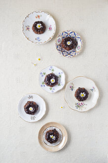 Mini chocolate cakes with edible flowers on plates - MYF001061