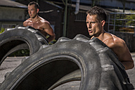Two CrossFit athletes exercising with tractor tyres - MADF000377