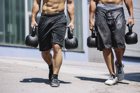 Two CrossFit athletes doing Farmer's Walk with kettlebells - MADF000382