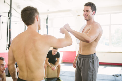 Two CrossFit athletes doing a fist bump after exercising - MADF000408