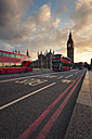UK, London, red buses passing Westminster Bridge with Big Ben tower in the background at sunset - ZM000402