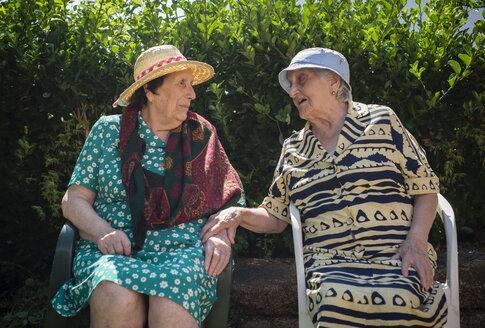 Two senior women communicating in the garden - RAEF000232