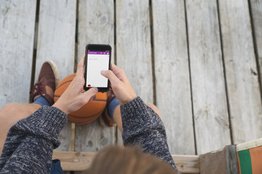 Teenage boy with basketball using smartphone - MEMF000834