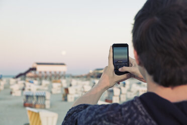 Germany, St Peter-Ording, teenage boy taking picture of full moon with his smartphone - MEMF000830