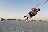 Germany, St Peter-Ording, teenager swinging on a swing at the beach - MEMF000837