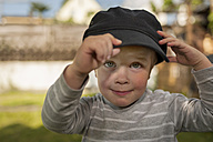 Portrait of little boy fitting cap of an adult - PAF001447