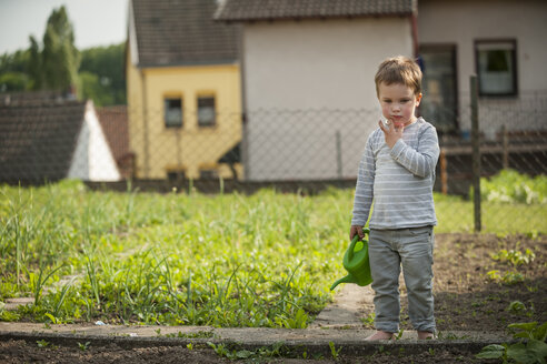 Pensive little boy standing in the garden with children's watering can - PAF001451
