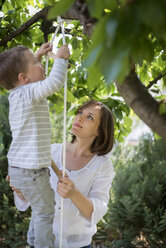 Mother helping her little son climbing up a rope ladder - PAF001461