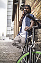 Germany, Cologne, portrait of young man with bicycle telephoning with smartphone - RIBF000130