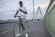Germany, Cologne, young man standing with bicycle on Rhine bridge looking at his smartphone - RIBF000152