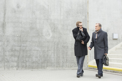 Two businessmen walking and talking outdoors - WESTF021366