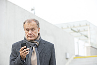 Businessman outdoors looking at cell phone - WESTF021327