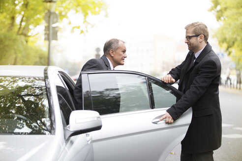 Chauffeur opening car door for businessman getting out - WESTF021377