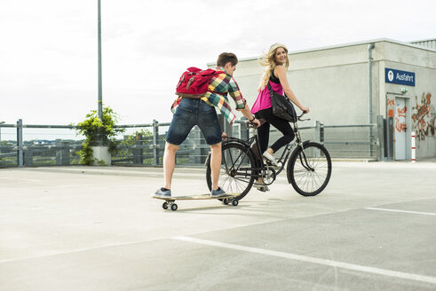 Happy young couple with bicycle and skateboard - UUF004861
