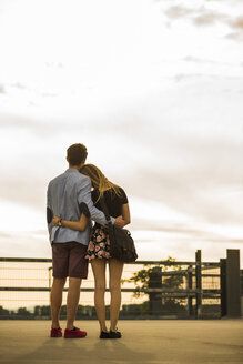 Young couple embracing on parking level at sunset - UUF004914