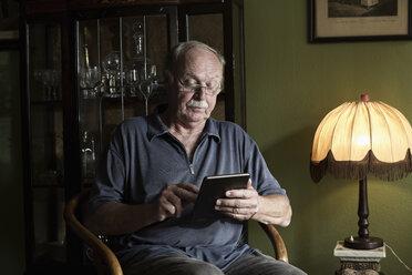 Senior man using mini tablet at home - MEMF000844