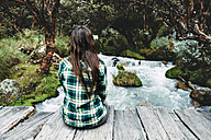 Peru, young woman sitting on a wooden bridge enjoying nature - GEMF000270