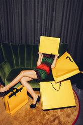 Young woman sitting on couch hiding her face behind a shopping bag - CHAF000535