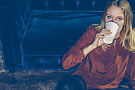 Young woman leaning on a couch drinking coffee to go - CHAF000543