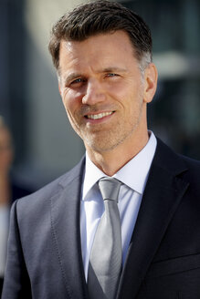 Portrait of smiling businessman with stubble - CHAF000354