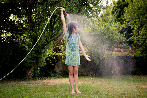Girl cooling herself with garden hose - LVF003675