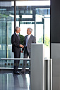 Two businessmen talking in office lobby - CHAF000369