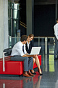 Businessman and businesswoman working on laptop in office lobby - CHAF001006