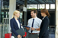 Three business colleagues discussing in office lobby - CHAF000376