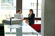 Businessman and businesswoman working on laptop in office lobby - CHAF000378